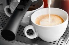 Kaffeemaschine, die heiße Milch im weißen Cup gießt Lizenzfreies Stockbild