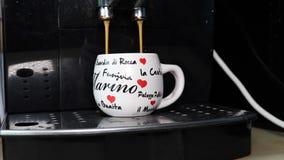 Kaffeemaschine, die Kaffee in einem Becher mit italienischen Wörtern verschüttet stock video footage