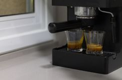 Kaffeemaschine, Kaffee in zwei Glasschalen auf einem Küchentisch produzierend stockfotografie