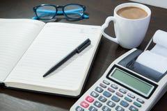 Kaffeenotizblock mit Stift- und Taschenrechnergläsern auf Arbeitstabelle Lizenzfreies Stockbild