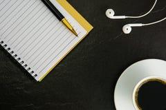 Kaffeenotizbuchkopfhörer auf einem schwarzen Hintergrund Stockfotografie