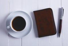 Kaffeenotizbuchstift auf hölzernem Hintergrund stockfotografie