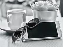 Kaffeepause mit Handy und Gläsern auf dem Tisch lizenzfreie stockbilder
