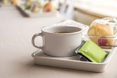Kaffeepause zwischen Sitzung und Snack auf Teller mit buntem bok Stockfotografie