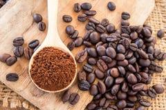 Kaffeepulver im hölzernen Löffel und in den Kaffeebohnen auf Holztisch Stockbilder