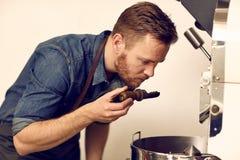 Kaffeeröster, der frisch das Aroma etwas Röstkaffees riecht Lizenzfreie Stockfotos