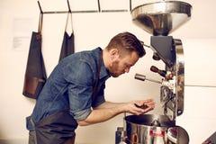Kaffeeröster, der frisch die Qualität von Kaffeebohnen roas überprüft Lizenzfreies Stockbild