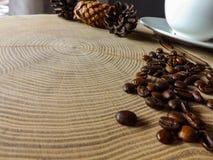Kaffeesamen und Kaffeetasse auf Holztisch stockbild