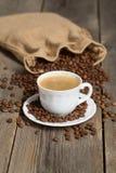 Kaffeetasche voll von Kaffeebohnen und von weißem Tasse Kaffee in der Front Stockbild