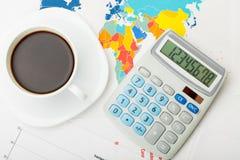 Kaffeetasse über Weltkarte und Finanzdokumente - Ansicht von der Spitze Lizenzfreie Stockbilder