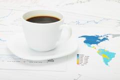 Kaffeetasse über Weltkarte und Finanzdokumenten Lizenzfreie Stockfotografie