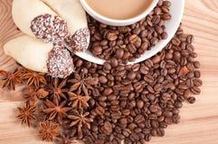 Kaffeetasse, Anis auf Kaffeebohnen, Bonbons auf dem hölzernen Hintergrund Lizenzfreie Stockbilder