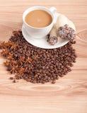 Kaffeetasse, Anis auf Kaffeebohnen, Bonbons auf dem hölzernen Hintergrund Stockfotos
