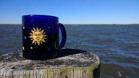Kaffeetasse auf Beitrag neben Meer Stockfotos