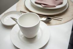 Kaffeetasse auf dem Teiltabellenspeisen Stockbild