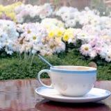 Kaffeetasse auf dem Tisch im Park Lizenzfreie Stockbilder