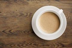 Kaffeetasse auf Draufsicht des Holztischs Stockbild
