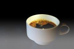 Kaffeetasse auf einem Glastisch Weißer Kaffeetasse-Abschluss oben mit dunklem Hintergrund und drastischem Licht Lizenzfreie Stockfotografie