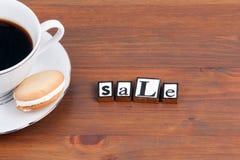Kaffeetasse auf einem Holztisch und einem Text - Verkauf Stockfoto