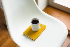 Kaffeetasse auf einem Stuhl Stockfotografie