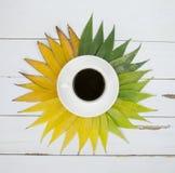 Kaffeetasse auf grünem Gelb verlässt Hintergrund Ebenenlage Stockfoto