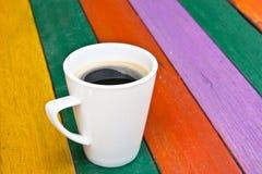 Kaffeetasse auf hölzernem buntem Stockbild
