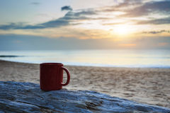Kaffeetasse auf hölzernem Klotz am Sonnenuntergang oder am Sonnenaufgangstrand Stockfoto