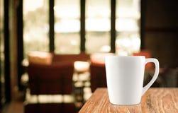 Kaffeetasse auf hölzerner Tabelle im Unschärfecaféhintergrund Stockbild