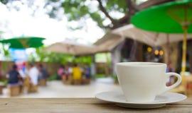 Kaffeetasse auf hölzerner Tabelle mit Unschärfekaffeestube Hintergrund stockfotos