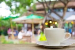 Kaffeetasse auf hölzerner Tabelle mit Unschärfekaffeestube Hintergrund lizenzfreie stockfotografie