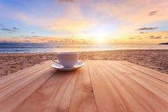 Kaffeetasse auf hölzerner Tabelle am Sonnenuntergang oder am Sonnenaufgangstrand