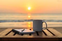 Kaffeetasse auf hölzerner Tabelle am Sonnenuntergang oder am Sonnenaufgangstrand Lizenzfreie Stockbilder