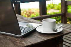 Kaffeetasse auf Holz mit Laptop. Stockbild