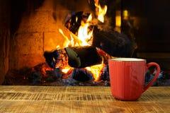 Kaffeetasse auf Holztisch über Kamin lizenzfreies stockfoto