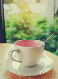 Kaffeetasse auf Holztisch mit grünem bokeh Lizenzfreie Stockfotos