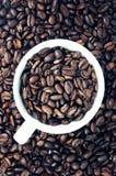 Kaffeetasse auf Kaffeebohnen Stockfoto