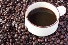 Kaffeetasse auf Kaffeebohnen stockfotografie