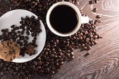 Kaffeetasse auf Kaffeebohnen mit Plätzchen Stockbilder