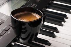 Kaffeetasse auf Klaviertastatur Stockfotografie