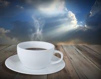 Kaffeetasse auf Schmutzholzfußboden mit Hintergrund des blauen Himmels Lizenzfreie Stockbilder