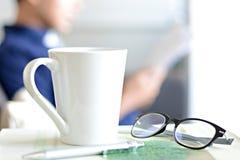 Kaffeetasse, Augengläser u. Stift über einem Buch mit Unschärfehintergrund eines Mannes Stockbild