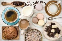 Kaffeetasse, Bohnen, Schokolade, Makronen, Milch, Brötchen, Zucker auf Holz lizenzfreie stockbilder