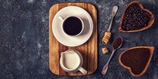 Kaffeetasse, Bohnen und Grundpulver auf Steinhintergrund Lizenzfreie Stockfotos