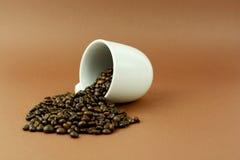 Kaffeetasse, die mit Kaffeebohnen auf braunen Hintergrund legt Lizenzfreie Stockfotos