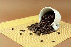 Kaffeetasse, die mit Kaffeebohnen auf placemat legt Lizenzfreie Stockfotografie
