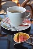 Kaffeetasse in einem Glastisch Stockfotografie