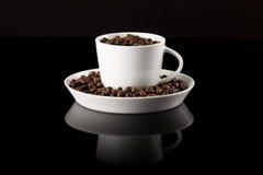 Kaffeetasse füllte mit Kaffee auf schwarzer reflektierender Oberfläche stockfotografie