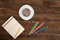 Kaffeetasse, farbige Bleistifte und ein Notizblock auf einem hölzernen Hintergrund Stockfotos
