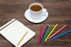 Kaffeetasse, farbige Bleistifte und ein Notizbuch Hölzerner Hintergrund Stockfotografie