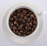 Kaffeetasse gefüllt mit Kaffeebohnen Lizenzfreie Stockfotografie